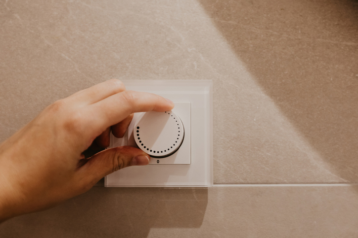Saving energy concept: Human hand turning down electrical light dimmer switch. - Image