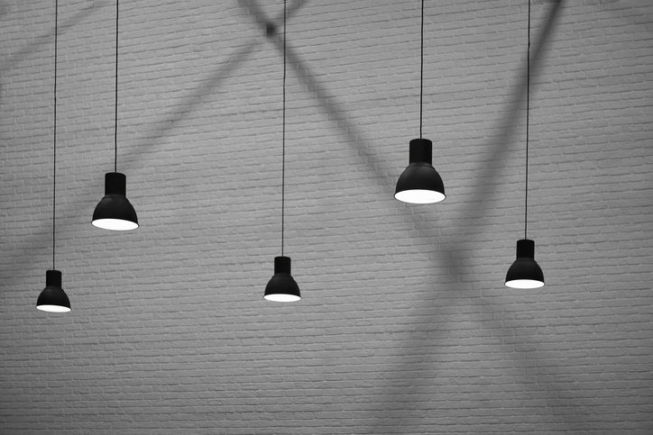Side view and selective focus of 5 hanging lamps with light and shadow on surface of brick wall background in black and white style, interior architecture design concept